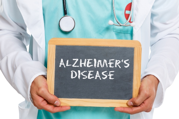 A doctor holds a sign that reads Alzheimer's Disease on it.