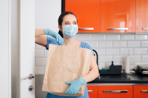 A home caregiver wears a protective face mask, gloves, and scrubs while helping to carry a grocery bag.